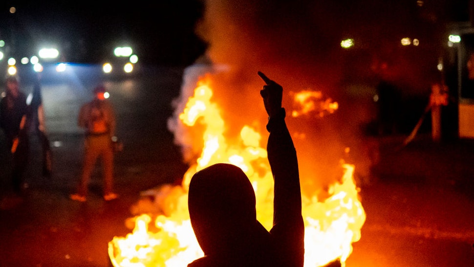 Protesters chant in front of a fire near the North police precinct during a protest against racial injustice and police brutality on September 6, 2020 in Portland, Oregon.