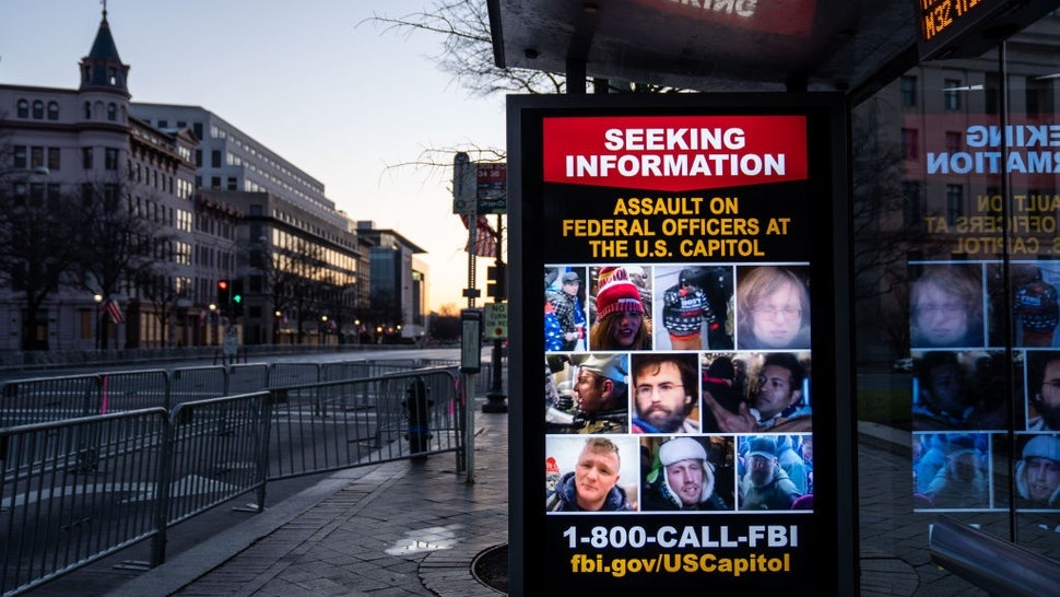 WASHINGTON, DC - JANUARY 16: A sign seeking information about people who breached the Capitol building is seen as the sun rises behind, seen from Pennsylvania Ave., which is within the secure area around downtown Washington DC on Saturday, Jan. 16, 2021 in Washington, DC. After last week's riots and security breach at the U.S. Capitol Building, the FBI has warned of additional threats in the nation's capital and across all 50 states.
