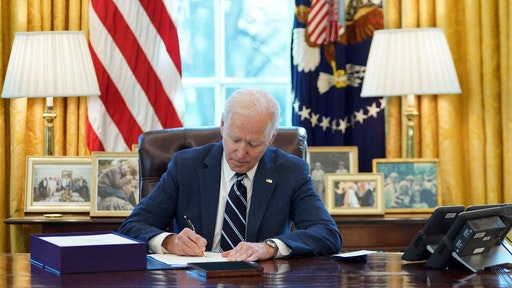 """US President Joe Biden signs the American Rescue Plan on March 11, 2021, in the Oval Office of the White House in Washington, DC. - Biden signed the $1.9 trillion economic stimulus bill and will give a national address urging """"hope"""" on the first anniversary of the start of the coronavirus pandemic. (Photo by MANDEL NGAN / AFP) (Photo by MANDEL NGAN/AFP via Getty Images)"""