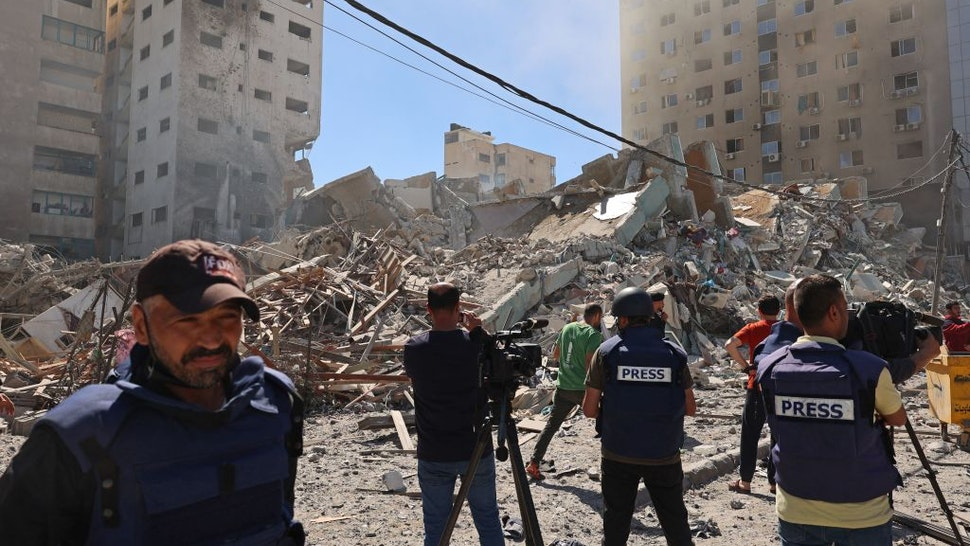 Palestinian journalists cover the destroyed Jala Tower, which was housing international press offices, following an Israeli airstrike in the Gaza Strip on May 15, 2021.