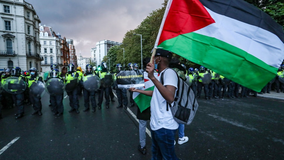 LONDON, UNITED KINGDOM - MAY 15 : A demonstrator carries a Palestinian flag in front of Metropolitan Police outside the Israeli Embassy in central London on Saturday, May 15, 2021. While Israeli bombardment of Gaza continued for a fifth consecutive day, this is the 3rd week of ongoing demonstrations across the United Kingdom with 25 demonstrations taking place across the country. (Photo by Vudi Xhymshiti/Anadolu Agency via Getty Images)