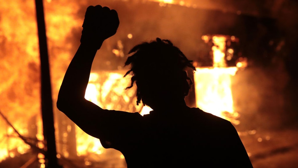 MINNEAPOLIS, MINNESOTA - MAY 29: A man raises his fist in front of a burning building during protests sparked by the death of George Floyd while in police custody on May 29, 2020 in Minneapolis, Minnesota. Earlier today, former Minneapolis police officer Derek Chauvin was taken into custody for Floyd's death. Chauvin has been accused of kneeling on Floyd's neck as he pleaded with him about not being able to breathe. Floyd was pronounced dead a short while later. Chauvin and 3 other officers, who were involved in the arrest, were fired from the police department after a video of the arrest was circulated. (Photo by Scott Olson/Getty Images)