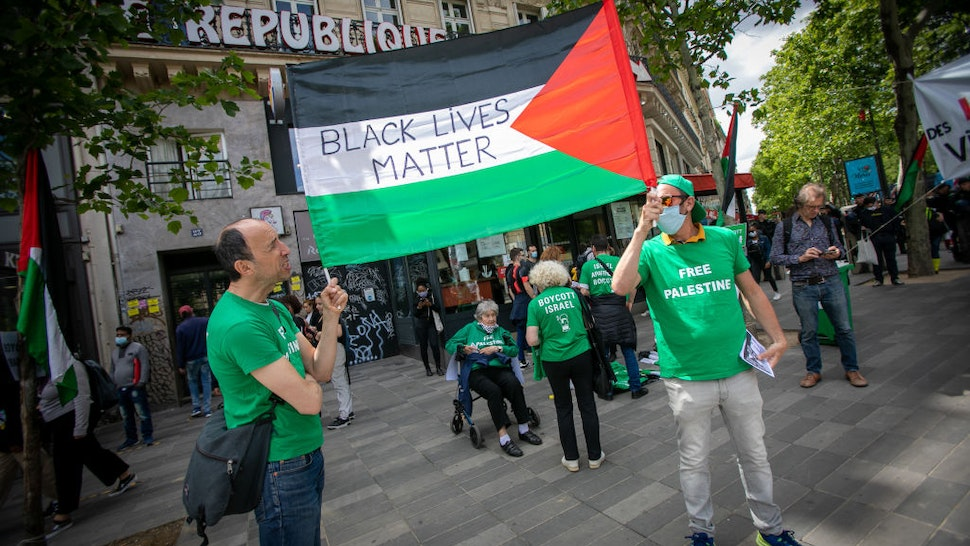 PARIS, FRANCE - JUNE 13: A banner on the palestinian flag is carried during a rally as part of the 'Black Lives Matter' worldwide protests against racism and police brutality on Place de la Republique on June 13, 2020 in Paris, France. People gathered in support of Adama Traore, a Malian French man who died in 2016 after being restrained by police in Paris. (Photo by Marc Piasecki/Getty Images)