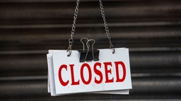 """CARDIFF, UNITED KINGDOM - JUNE 20: A closed sign hanging in the window of a closed small business on June 20, 2020 in Cardiff, United Kingdom. The First Minister of Wales Mark Drakeford has continued the easing of the lockdown in Wales, announcing that all non-essential shops will be allowed to open their doors again and outdoor sports courts can re-open. Team and contact sports will not be permitted and playgrounds will remain closed. People will be asked to continue to """"stay local"""" with five miles given as guidance until July 6."""