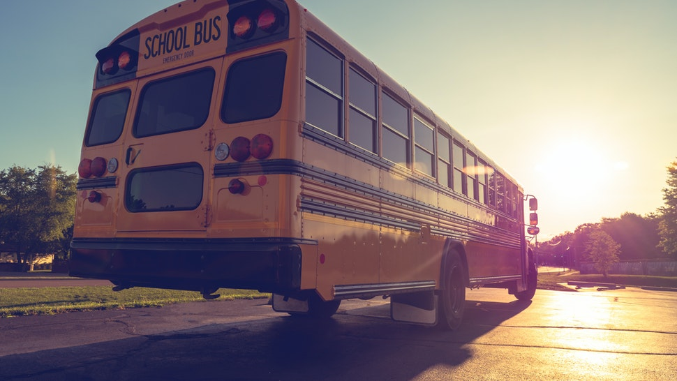 Low angle view of yellow school buss from right rear at dusk looking into setting sun