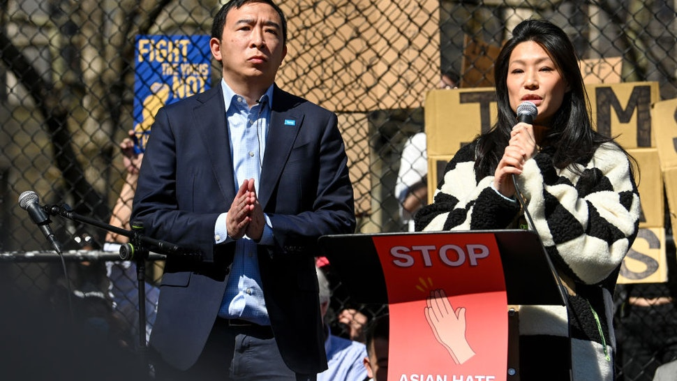 """NEW YORK, NEW YORK - MARCH 21: New York City Mayoral candidate Andrew Yang stands next to his wife, Evelyn Yang, while she speaks at the """"Rally Against Hate"""" in Columbus Park, Chinatown on March 21, 2021 in New York City. Stop Asian Hate rallies have been happening in New York City and other parts of the country after a year of that has seen a rise in hate crimes towards Asian Americans and the attack in Atlanta, Georgia on March 16, 2021 that left eight people dead, including six Asian women."""