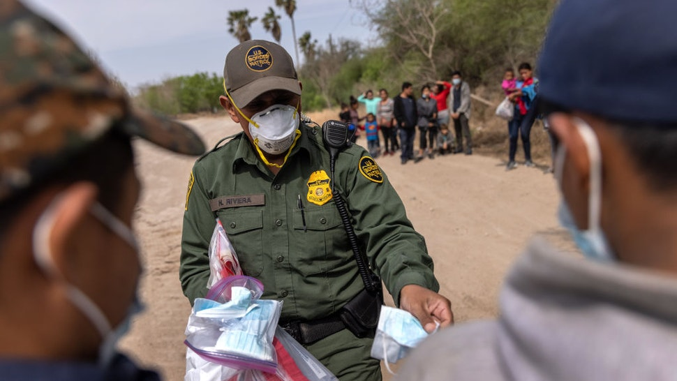 HIDALGO, TEXAS - MARCH 25: A U.S. Border Patrol agent hands out masks to unaccompanied minors after a group of asylum seekers crossed the-Rio Grande into Texas on March 25, 2021 in Hidalgo, Texas. A large group of families and unaccompanied minors, mostly teenagers, came across the border onto private property, where Border Patrol agents took aside the unaccompanied minors for separate transport. The Biden administration is permitting minors to stay in the U.S., whereas many families, especially with older children, are being deported. (Photo by John Moore/Getty Images)