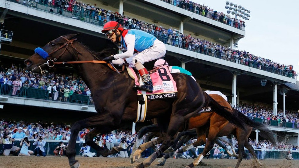LOUISVILLE, KENTUCKY - MAY 01: Medina Spirit #8, ridden by jockey John Velazquez, (R) crosses the finish line to win the 147th running of the Kentucky Derby ahead of Mandaloun #7, ridden by Florent Geroux, and Hot Rod Charlie #9 ridden by Flavien Prat , and Essential Quality #14, ridden by Luis Saez, at Churchill Downs on May 01, 2021 in Louisville, Kentucky. (Photo by Tim Nwachukwu/Getty Images)