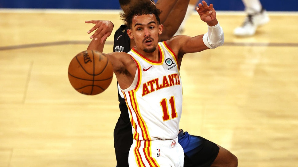 NEW YORK, NEW YORK - MAY 26: Trae Young #11 of the Atlanta Hawks passes the ball as Alec Burks #18 of the New York Knicks defends in the fourth quarter during game two of the Eastern Conference Quarterfinals at Madison Square Garden on May 26, 2021 in New York City.The New York Knicks defeated the Atlanta Hawks 101-92. NOTE TO USER: User expressly acknowledges and agrees that, by downloading and or using this photograph, User is consenting to the terms and conditions of the Getty Images License Agreement. (Photo by Elsa/Getty Images)
