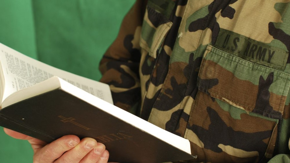 Army soldier holding Bible