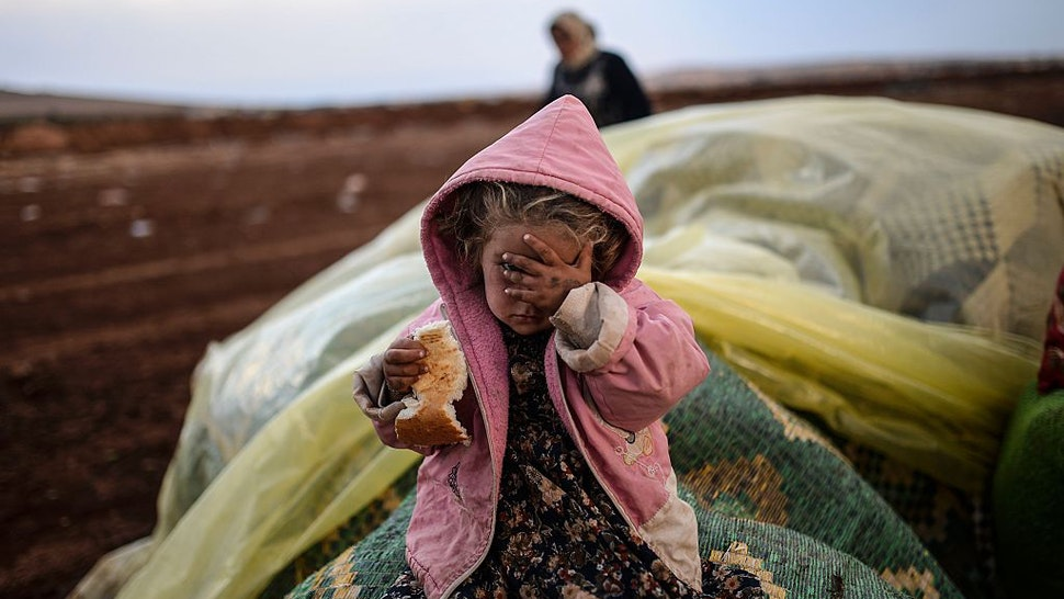 A Syrian Kurdish woman wait with her daughter near the Syria border at the southeastern town of Suruc in the Sanliurfa province after crossing the border between Syria and Turkey after several mortars hit both sides on October 2, 2014. Islamic State fighters are pushing towards a key Kurdish town on Syria's border with Turkey, whose parliament is set on October 2 to consider authorising military intervention against the jihadists on its doorstep. Kurdish fighters backed by US-led air strikes were locked in fierce fighting Wednesday to prevent the besieged border town of Ain al-Arab from falling to the Islamic State group fighters. AFP PHOTO/BULENT KILIC / AFP / BULENT KILIC (Photo credit should read BULENT KILIC/AFP via Getty Images)