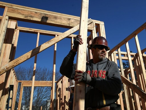 PETALUMA, CA - JANUARY 21: A worker carries lumber as he builds a new home on January 21, 2015 in Petaluma, California. According to a Commerce Department report, construction of new homes increased 4.4 percent in December, pushing building of new homes to the highest level in nine years.