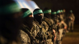 TOPSHOT - Palestinian members of the Ezzedine al-Qassam Brigades, the armed wing of the Hamas movement, take part in a gathering on January 31, 2016 in Gaza city to pay tribute to their fellow militants who died after a tunnel collapsed in the Gaza Strip.