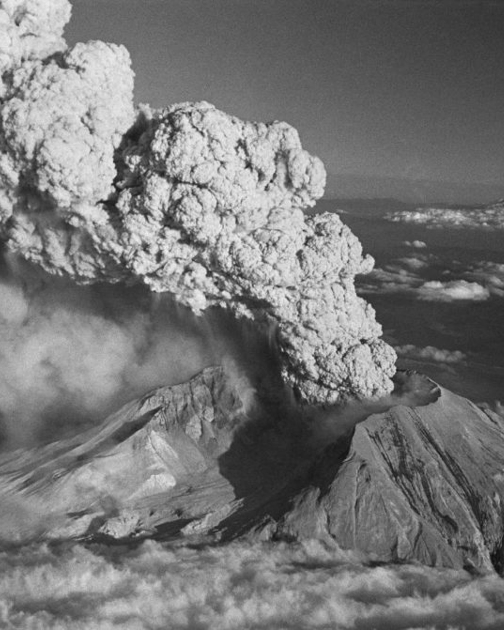 """(Original Caption) """"BLOWS TOP AGAIN."""" SPIRIT LAKE,WASH.: WITH MOUNT HOOD (RIGHT,REAR) VISIBLE IN THE BACKGROUND, MOUNT ST.HELENS ERUPTS JULY 22. THE PLUME OF STEAM AND ASH ROSE SOME 60,000 FEET IN THE AIR, SENDING ASH IN A NORTHEASTERLY DIRECTION. MOUNT ST.HELENS BROKE A SIX-WEEK SILENCE WITH A SERIES OF TOWERING ASH ERUPTIONS. JULY 29,1980."""