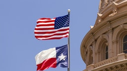 US and Texas flags flying over Texas State Capitol building, Austin, USA