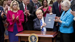U.S. President Donald Trump holds up H.J. Res. 58, which overturns a rule requiring states to report specific information on teacher preparation programs, such as student learning outcomes, and rate their effectiveness, after signing the bill during a ceremony in the Roosevelt Room of the White House in Washington, D.C., U.S., on Monday, March 27, 2017. Trump signed four bills, H.J. Res 37, H.J. Res 44, H.J. Res. 57 and H.J. Res. 58, that nullify measures put in place during former President Obama's administration.