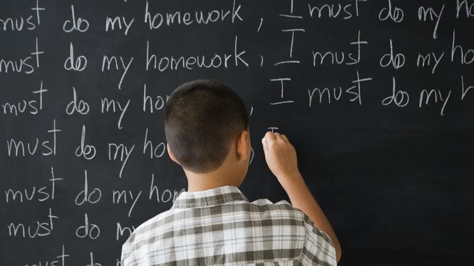 Rear view of boy writing on blackboard - stock photo
