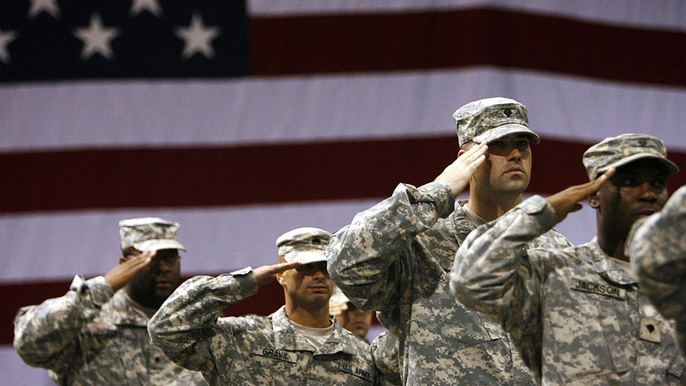 FORT RILEY, KS - SEPTEMBER 12: Soldiers stand saluting during the national anthem for the redeployment ceremony at Marshall Army Air Field inside hanger 727 for the 1st Battalion, 16th Infantry Regiment, 1st Brigade, 1st Infantry Division September 12, 2007 at Fort Riley, Kansas. The approximately 130 soldiers were returning after a one year tour in Iraq.