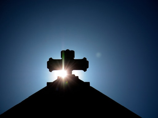 SANTA FE, NM - JULY 29, 2017: The morning sun rises behind a stone cross atop The Cathedral Basilica of St. Francis of Assisi, commonly known as Saint Francis Cathedral, in Santa Fe, New Mexico. Built between 1869 and 1886, the Roman Catholic Church is the mother church of the Archdiocese of Santa Fe. (Photo by Robert Alexander/Getty Images)