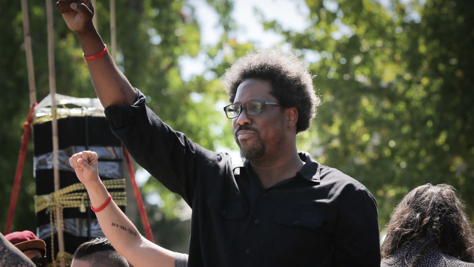 BERKELEY, CA - AUGUST 27: Comedian W. Kamau Bell raises his fist from a truck as people begin to march from MLK Jr. Park on August 27, 2017 in Berkeley, California. (Photo by Elijah Nouvelage/Getty Images)