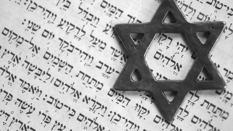 """Star of David over the first page of the old testament in Hebrew. The word in the center of the star means """"God""""."""