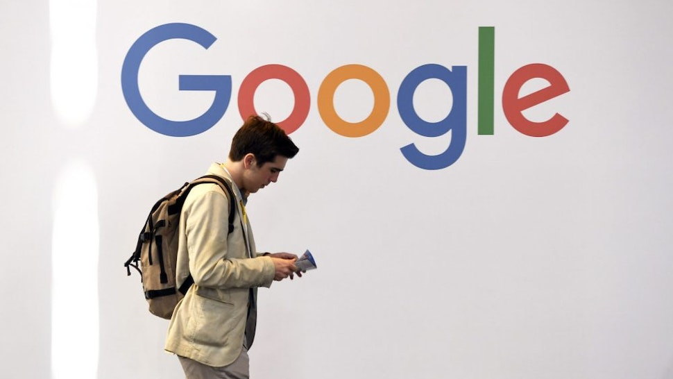 A man walks past the logo of the US multinational technology company Google during the VivaTech trade fair ( Viva Technology), on May 24, 2018 in Paris.