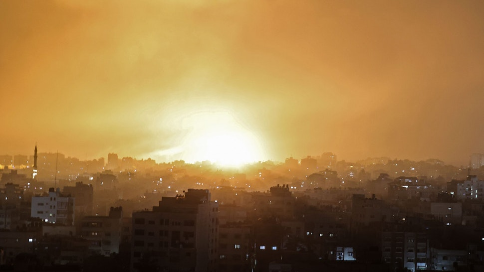 TOPSHOT - An explosion lights the sky following an Israeli air strike on Beit Lahia in the northern Gaza Strip on May 14, 2021.