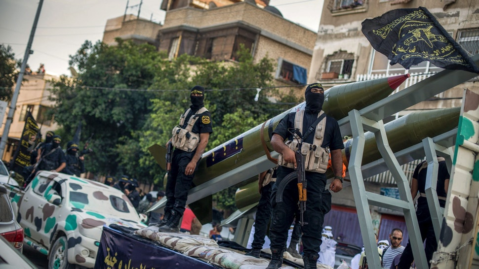 GAZA, GAZA CITY, PALESTINE - 2018/10/04: Military officers are seen on top of the truck holding guns during the march. Members of the Palestinian Al-Quds Brigades, the military wing of the Islamic Jihad group march in the streets of Gaza city with their weapons to show loyalty for the Iranian-backed Palestinian movement's newly elected leader Ziad al-Nakhalah.