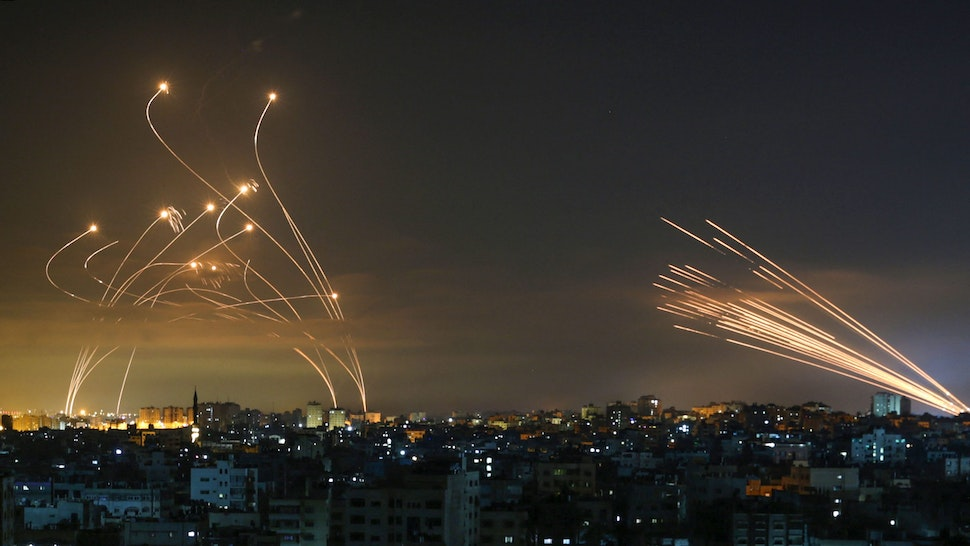 """Rockets are seen in the night sky fired towards Israel from Beit Lahia in the northern Gaza Strip on May 14, 2021. - Israel bombarded Gaza with artillery and air strikes on Friday, May 14, in response to a new barrage of rocket fire from the Hamas-run enclave, but stopped short of a ground offensive in the conflict that has now claimed more than 100 Palestinian lives. As the violence intensified, Israel said it was carrying out an attack """"in the Gaza Strip"""" although it later clarified there were no boots on the ground."""