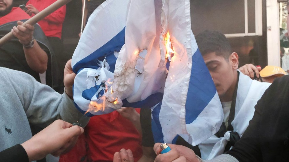 NEW YORK, NY - MAY 20: Pro Palestinian protesters burn the Israeli flag as they face off with a group of Israel supporters and police in a violent clash in Times Square on May 20, 2021 in New York City. Despite an announcement of a cease fire between Israel and Gaza militants, dozens of supporters of both sides of the conflict fought in the streets of Times Square. Dozens were arrested and detained by police before they were dispersed out of the square. The 11 days of fighting has claimed the lives of at least 232 people in Gaza and 12 in Israel.