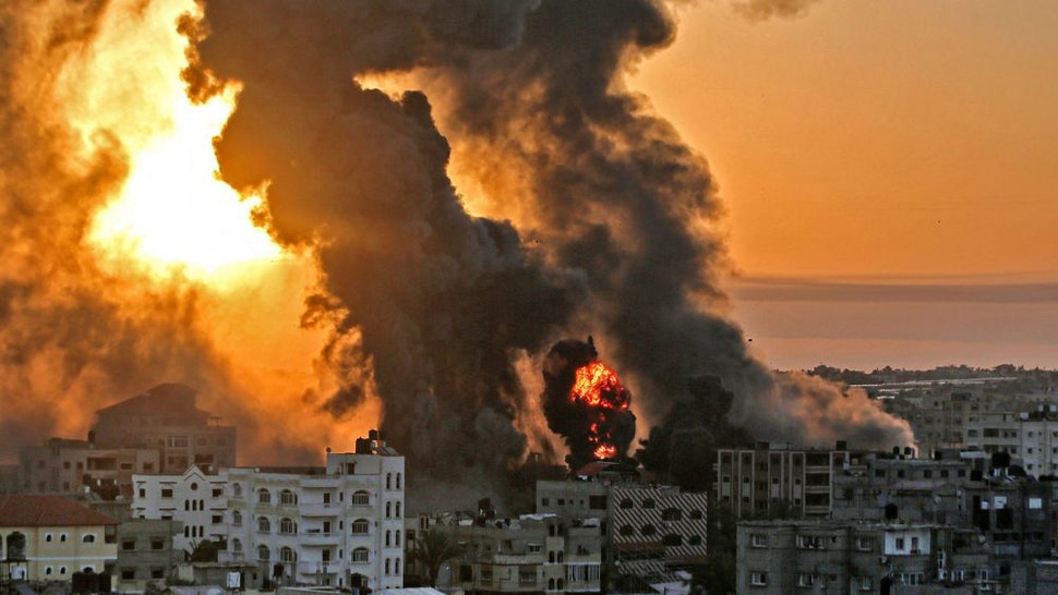 TOPSHOT - A fire rages at sunrise in Khan Yunish following an Israeli airstrike on targets in the southern Gaza strip, early on May 12, 2021. - Israeli air raids in the Gaza Strip have hit the homes of high-ranking members of the Hamas militant group, the military said Wednesday, with the territory's police headquarters also targeted.