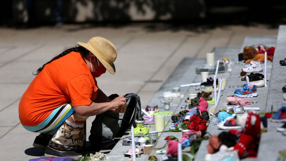 VANCOUVER, CANADA - MAY 29 : A woman mourns over 215 pairs of kids shoes outside Vancouver Art Gallery during a memorial on May 29, 2021 in Vancouver, British Columbia, Canada The remains of 215 children have been found buried at a Canadian residential school, an Indigenous band confirmed Thursday.