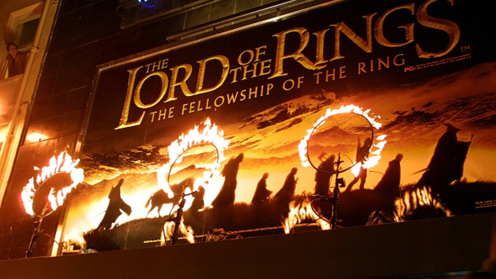 """Rings of fire burn near the movie poster for the film """"The Lord of the Rings: The Fellowship of the Ring."""" The stars of the film attended the premiere in London."""