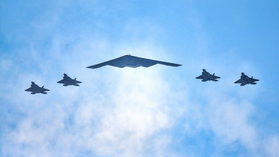 """NEW YORK, NY - JULY 04: F-22 Raptors and a B-2 Stealth Bomber (C) fly over the Hudson River during the """"Salute to America"""" military flyover on July 4, 2020 in New York City."""