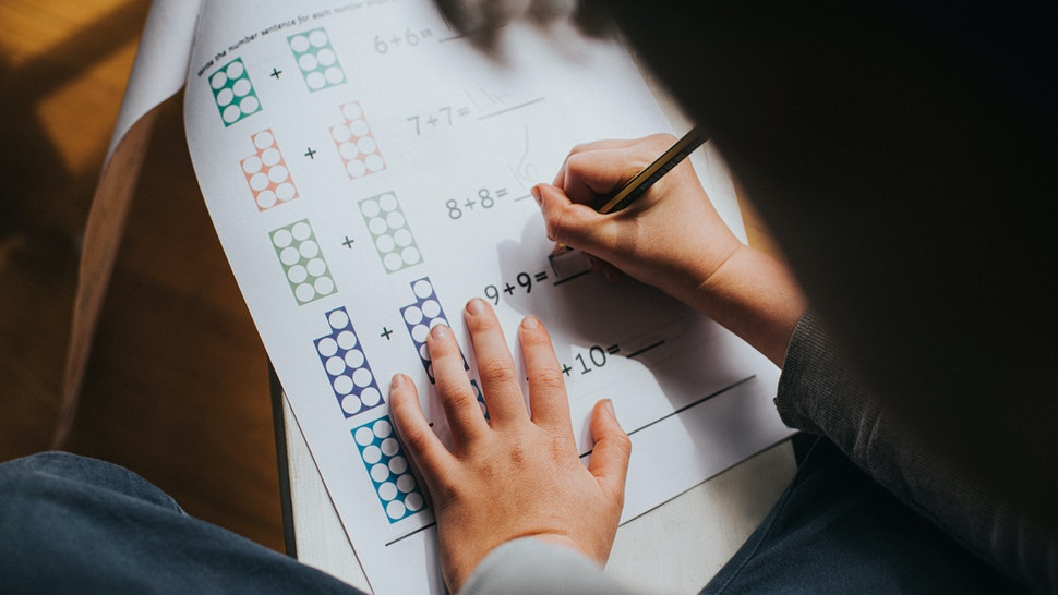 Child adding numbers on a printed maths sheet of homework. Space for copy.