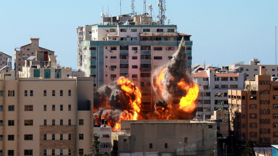 A ball of fire erupts from the Jala Tower as it is destroyed in an Israeli airstrike in Gaza city controlled by the Palestinian Hamas movement, on May 15, 2021. - Israeli air strikes pounded the Gaza Strip, killing 10 members of an extended family and demolishing a key media building, while Palestinian militants launched rockets in return amid violence in the West Bank. Israel's air force targeted the 13-floor Jala Tower housing Qatar-based Al-Jazeera television and the Associated Press news agency.