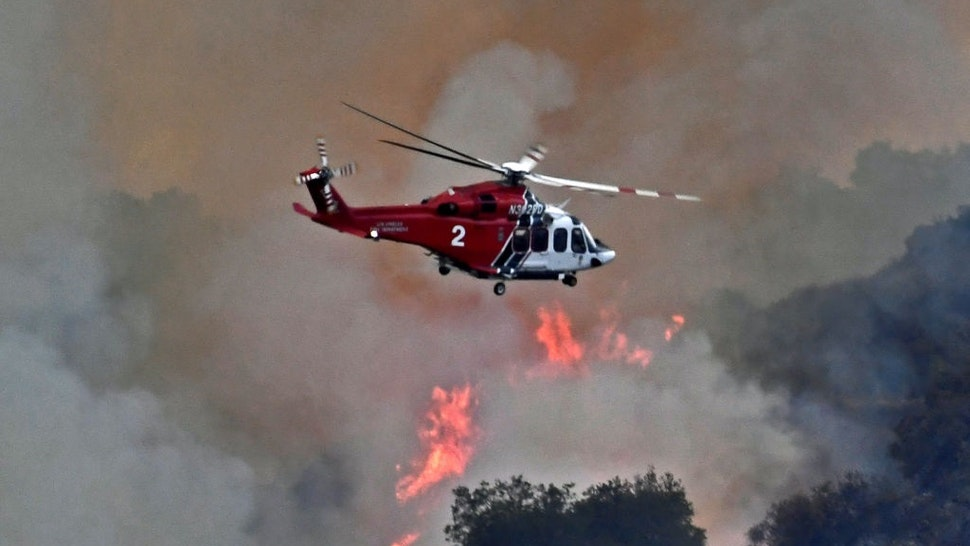 PACIFIC PALISADES, CA - MAY 16: A helicopter flies over as firefighters continue to battle a 1,325-acre brush fire May 16, 2021 near Pacific Palisades, California.