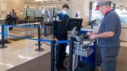 SANTA ANA, CA - JANUARY 26: A TSA agent helps a man through a security checkpoint at John Wayne Airport in Santa Ana, CA on Tuesday, January 26, 2021.