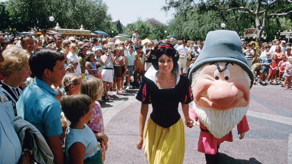 A crowd gathers to watch Snow White and Grumpy on a sunny day at Disneyland. Anaheim, California, 1969