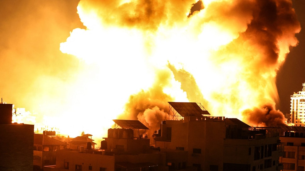 A ball of fire explodes above buildings in Gaza City as Israeli forces shell the Palestinian enclave, early on May 18, 2021. - Israeli jets kept up a barrage of air strikes against the Palestinian enclave of Gaza as a week of violence that has killed more than 200 people pushed world leaders to step up mediation.