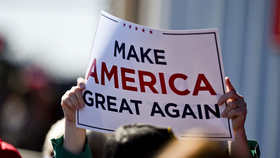 """A supporter holds a """"Make America Great Again"""" sign. At the Reading Regional Airport in Bern township Saturday October 17, 2020 where Vice President Mike Pence made a stop in Air Force 2 for a campaign rally."""