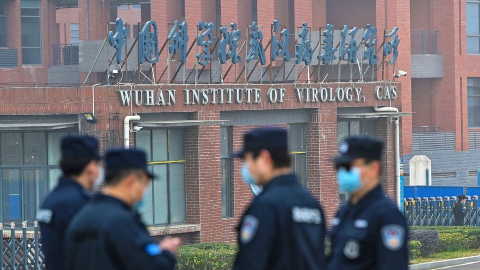 Security personnel stand guard outside the Wuhan Institute of Virology in Wuhan as members of the World Health Organization (WHO) team investigating the origins of the COVID-19 coronavirus make a visit to the institute in Wuhan in China's central Hubei province on February 3, 2021.
