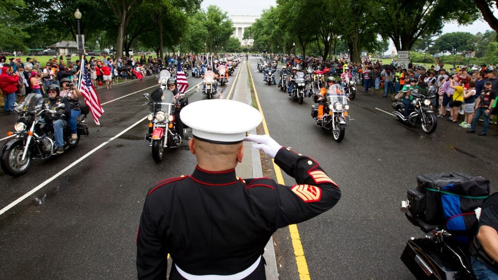 TOPSHOT - US Marine Tim Chambers salutes as participants in the Rolling Thunder annual motorcycle rally ride in Washington DC, on May 28, 2017. Motorcyclists are in Washington for the traditional annual Rolling Thunder ahead of Memorial Day, May 29. / AFP PHOTO / Jose Luis Magana (Photo credit should read