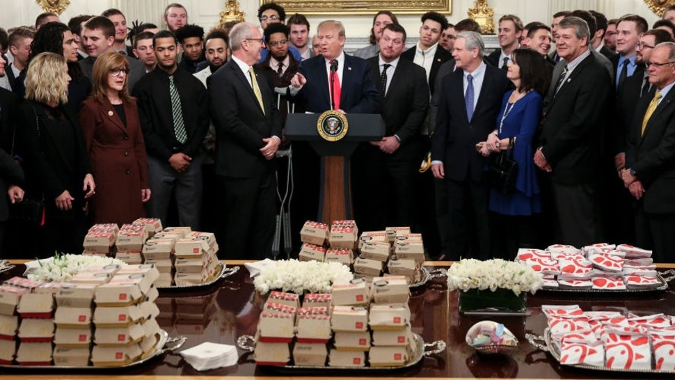 WASHINGTON, DC - MARCH 4: (AFP OUT) U.S. President Donald Trump speaks behind a table full of McDonald's hamburgers, Chick fil-a sandwiches and other fast food as he welcomes the 2018 Football Division I FCS champs North Dakota State Bison in the Diplomatic Room of the White House on March 4, 2019 in Washington, DC. (Photo by