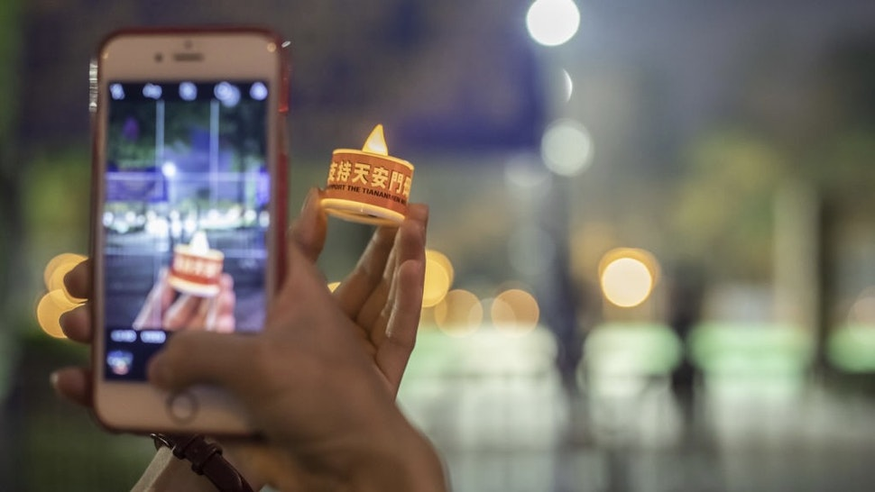 Hong Kong Police Bans Annual Tiananmen Vigil For The Second Straight Year A person takes a photo of an electronic candle outside Victoria Park, the traditional site of the annual Tiananmen candlelight vigil, in Hong Kong, China, on Friday, June 4, 2021. Hong Kongpolice on Friday warned democracy activists trying to commemorate Chinas deadly Tiananmen Square crackdown in 1989 that they could be violating the sweeping national security law imposed by China. Photographer: Paul Yeung/Bloomberg via Getty Images Bloomberg / Contributor via Getty Images