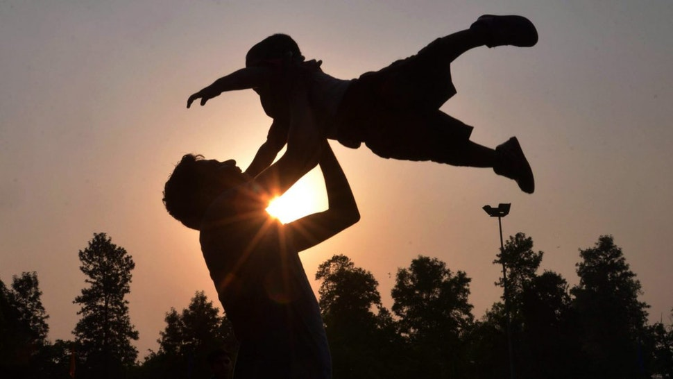 Indian father Shailesh throws up his son, Harish, at a park in Amritsar on June 19, 2016, on Father's Day, a day observed in many countries to celebrate fathers and fatherhood.
