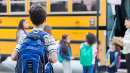 Rear view of elementary age boy waiting to get on school bus. His classmates are loading the bus in the background.