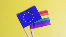 Small LGBT and EU flags on yellow background - stock photo Small LGBT and EU flags on yellow background close up Vera Aksionava via Getty Images