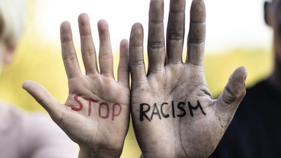 """""""Stop racism"""" concept, written on the hands of two multiethnic friends - stock photo Multiethnic friends holding their hands with written slogan """"Stop racism"""" Vladimir Vladimirov via Getty Images"""