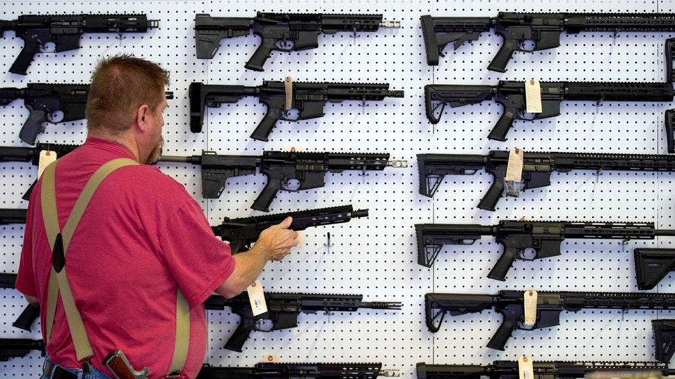 A worker restocks AR-15 guns at Davidson Defense in Orem, Utah on March 20, 2020. - Gun stores in the US are reporting a surge in sales of firearms as coronavirus fears trigger personal safety concerns.